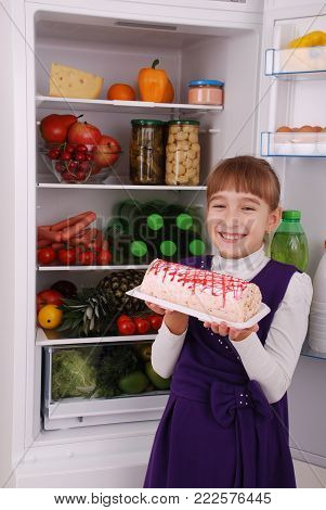 Girl is holding a banana on the refrigerator background. Beautiful  girl near the Fridge with healthy food. Fruits and vegetables in the refrigerator.