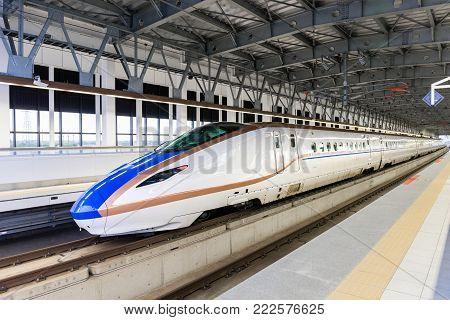 TOYAMA, JAPAN - MAY 16, 2016: The HOKURIKU Shinkansen Bullet Train (W7 Type) approaches at a platform at JR Shin-Takaoka station. Hokuriku Sinkansen is a high speed railway line opened in March 2015.