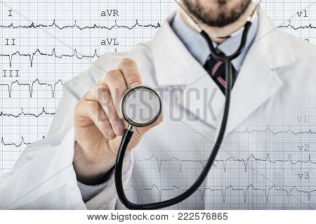 Male cardiologist doctor showing stethoscope for checkup with electrocardiogram in background