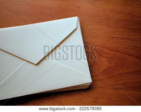 White Blank Stationery Envelopes on Wood Grain Desk Mockup