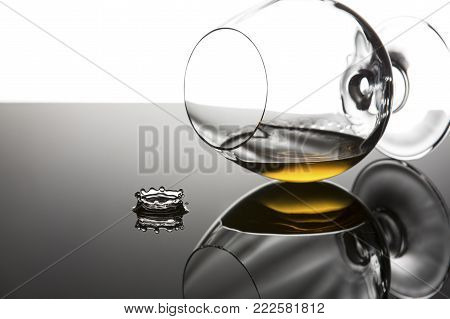 Brandy in a cognac glass lying on its side on a shiny surface with drop splash