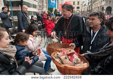 Florence, Tuscany, Italy - January 6, 2018: The Florentine Archbishop Cardinal Giuseppe Betori distributes gifts to the children to celebrate the Feast of Epiphany, during the historical recreation of the