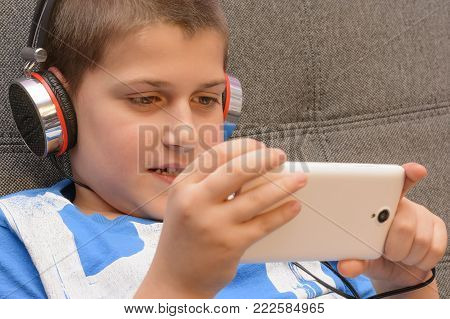Boy With Headphones And Mobile Phone In Hand