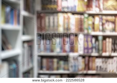 Blurred library, bookstore bookshelfs with colorful books, manuals and textbooks. Education, school, study concept. For abstract background