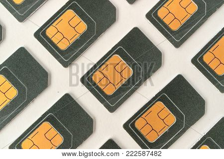 SIM card lying at an angle, a lot of SIM cards, grey