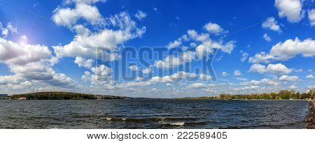 breathtaking scenery. many fluffy clouds in the blue sky over the water. hectic urban lake. panorama