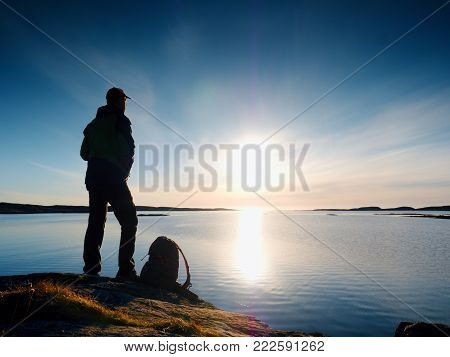 Young standing man with backpack. Hiker on the stone on the seashore at colorful sunset sky. Beautiful landscape with sporty man rocks sea and clouds at sunset. Sporty lifestyle