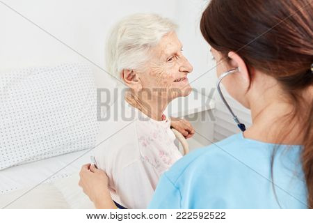 Caregiver examines old female patient with stethoscope in nursing home