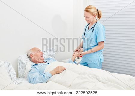 Nurse cares for bedridden senior in hospital or nursing home