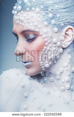 Fantasy make-up. Portrait of beautiful woman with fantasy make-up with white pearls on a grey background