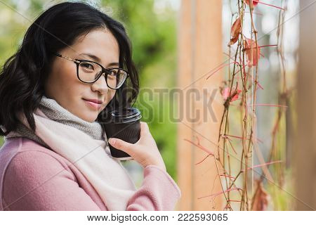 Portrait of beautiful young asian woman drinking hot drink from disposable paper cup outdoors. A girl with glasses looks at the camera.