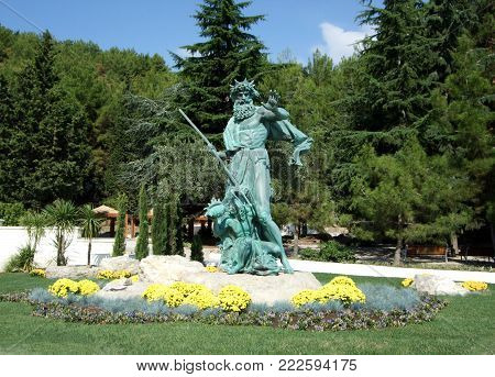 Partenit, Crimea, Russia - JULY 15, 2012: Statue Neptune holds a trident and a girl is a seashell in Aivazovsky park. Partenit park. Suuny day. Crimea. Russia