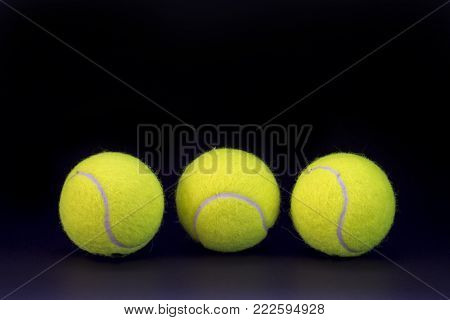 Yellow tennis balls on black background. Tennis ball abstract photo for banner template. Sport equipment isolated. Tennis competition backdrop. Yellow felt ball for active game. Outdoor sport activity