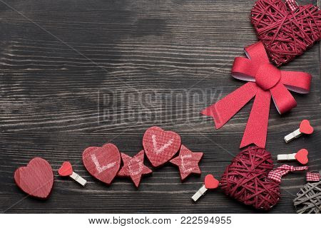 Love and Valentines day concept. Hearts, bow, stars and pegs in red color, top view. Valentines decorations and symbols on vintage wooden background with copy space.