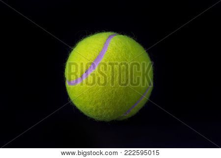 Felt tennis ball isolated on black background. Tennis ball photo for banner template. Sport equipment isolated. Tennis competition backdrop. Yellow felt ball for active game. Summer sport activity
