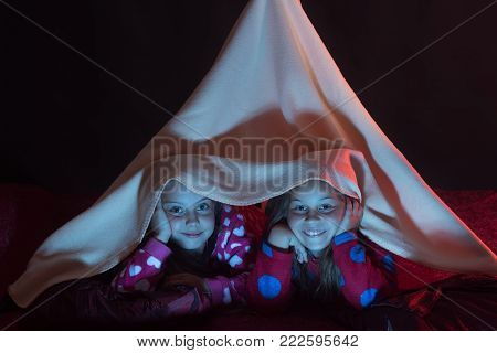 Girls with happy faces lie under pink blanket tent. Childhood and bedtime concept. Kids in pajamas covered with blanket lie on black background. Children have pajama party.