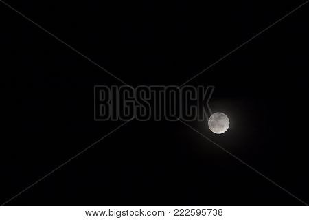Full moon on dark night sky. Skyscape with moon phase in equator. Black and white night sky photo. Moon relief. Space light in darkness. Cosmic banner template. Earth natural satellite telescopic view
