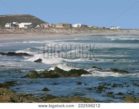 FROM YZERFONTEIN, CAPE TOWN, SOUTH AFRICA, A SEASCAPE WITH TURQUOISE, BLUE WATER AND A FEW WHITE WAVES IN THE FORE GROUND AND HOUSES AND A HILL IN THE BACK GROUND