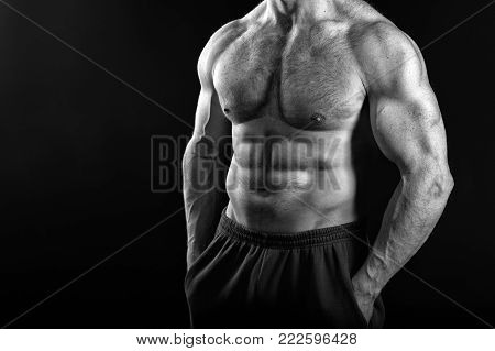 Coach sportsman with bare chest. Man with muscular body and torso. Dieting and fitness, health. Sport workout. Athletic bodybuilder in pants isolated on black background, copy space, black and white