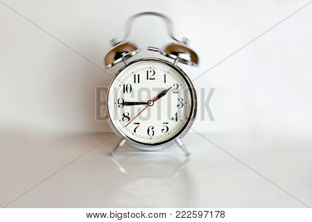 White retro clock isolated against a white background casting a reflection