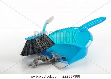 spring cleaning concept, blue hand brush and dustpan sweeping dust bunnies, copy space, light gray background fading to white, selected focus, narrow depth of field