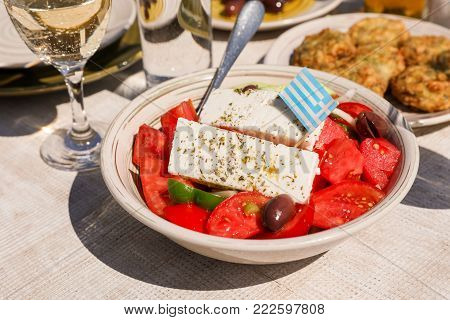 A bowl of village greek salad with greek flag on next to zucchini balls plate and white wine, water glasses served in greek tavern. Horizontal. Daylight. Close-up.