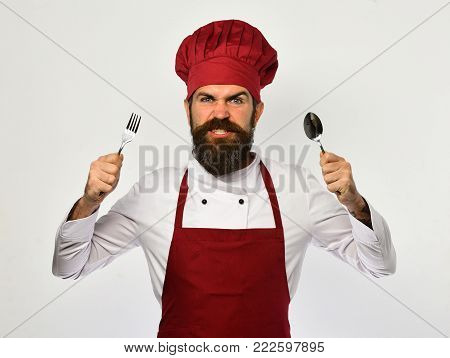 Man With Beard Holds Fork And Spoon On White Background.