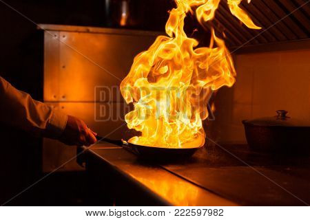Flambe lamb rib roast. Cooking with fire in frying pan. Professional chef in a commercial kitchen cooking. Man frying food in flaming pan on hob in outdoor kitchen. slow motion .