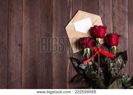 Valentines day envelope love letter with greeting card mothers day red rose gift surprise on dark wooden background with copyspace. Love flower gift for woman romantic holiday birthday