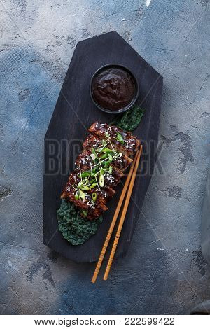 Barbecue pork ribs on wooden board, top view.