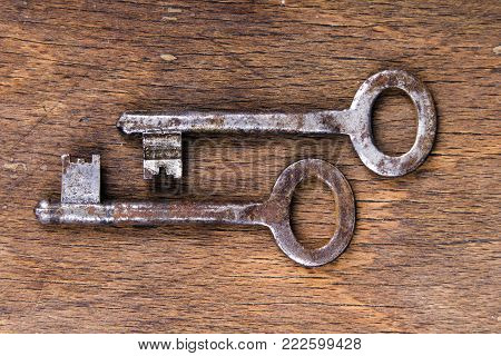 Old rusty keys on wooden background, copy space