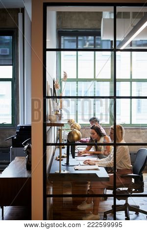 Business team working in an office booth, vertical