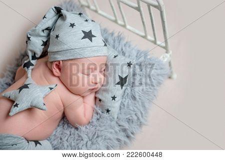 Sweet newborn boy on small cot sleeping