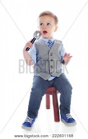 A handsome young boy speaking or singing into a microphone as he sits on a stool. Isolated on white.