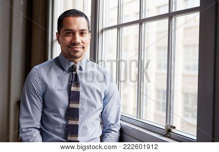 Young Hispanic business man smiling to camera