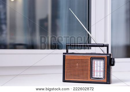 Old Brown Retro Radio Is On The White Window Sill Of The Room From The Directional Antenna