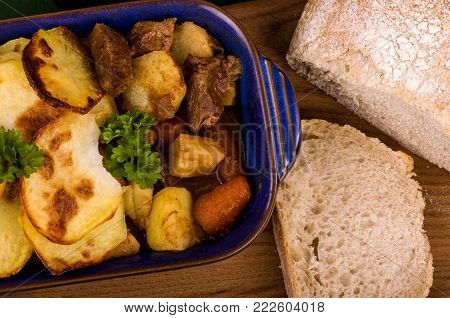 Beef in Irish Stout Stew A dish of Beef in Irish stout with a topping of sliced potatoes, served with a selection of vegetables and Sourdough bread, with stout battered onion rings and a jug of onion gravy. A St. Patrick's Day favourite.