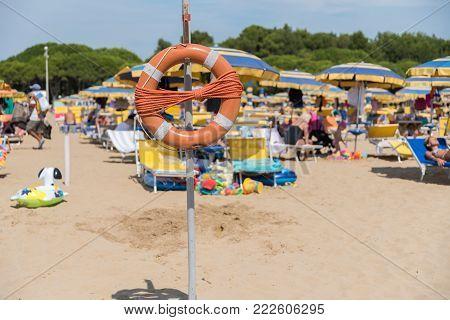 orange lifebuoy with many bathers on the sandy beach