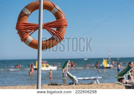 orange lifebuoy on the sandy beach and sea view