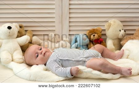Infant With Blue Eyes And Peaceful Smile Among Teddy Bears
