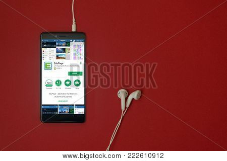 Los Angeles, January 11, 2018: Smartphone with Edupage application in google play store on red background with earphones plugged in and copy space