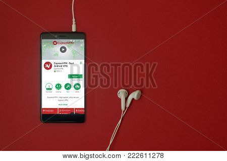 Los Angeles, January 11, 2018: Smartphone with Express VPN application in google play store on red background with earphones plugged in and copy space