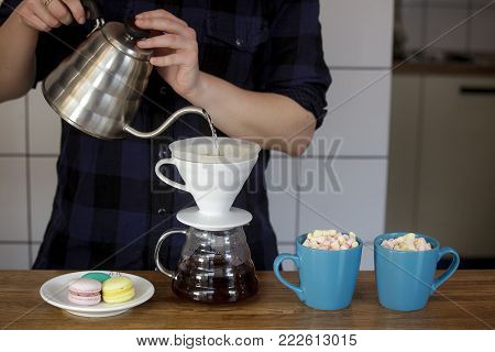 The hands of a woman make tea. Only hands pour tea. Next to the tea are two blue crusts with chocolate and marshmallows.