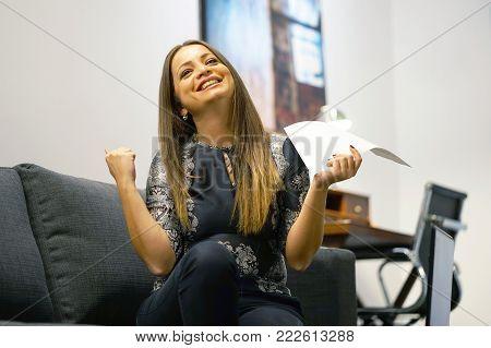 Happy woman enjoying good news in written notice. Euphoric girl happy after reading good news in written letter, loan approvale.