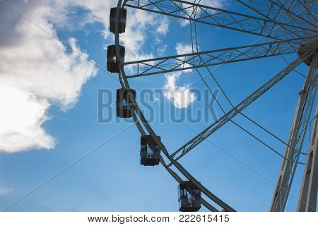 Ferris wheel. Carousel against the blue sky and white clouds. Benches. Lines that go into perspective.