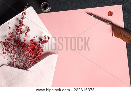 Envelope with flowers on a paper and a quill pen - Romantic frame with an envelope full of red flowers, on a blank paper sheet, near an ink bottle and an old feather pen, on a black wooden table.