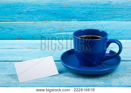 Blank business cards, blue cup on the wooden table. Template for ID. Top view