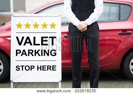 Close-up Of Male Valet Standing Near Valet Parking Sign
