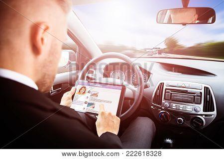 Businessman Chatting On Social Media Site Sitting Inside Self Drive Car