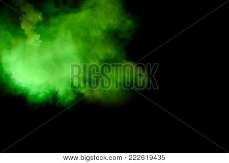 Colorful green smoky isolated on black background. Smoke bomb is pyrotechnic means for starting to fog, designed to supply signals that indicate pick-up masking of objects (including riots).